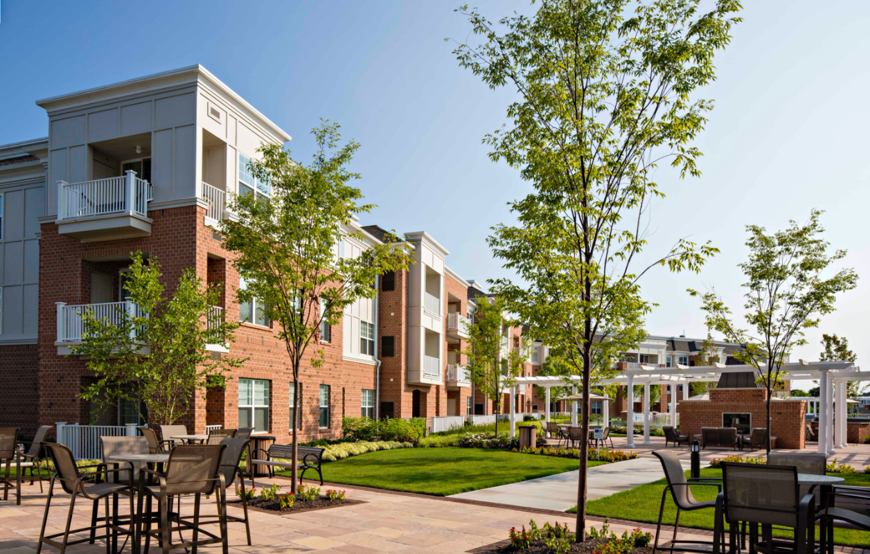 photo of exterior courtyard at Highlands at Hilltop apartments by RHO Residential in Verona, NJ with trees, tables and chairs, outdoor fireplace and building in background